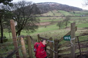 Walker at gate with Great Mell Fell in background