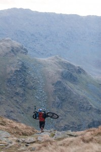 A mountain bike rider climbs up from Small Water to Nan Bield Pass, Haweswater