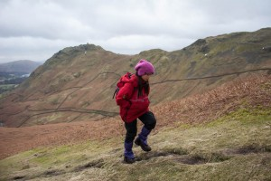 Hannah climbs Steel Fell with Helm Crag in background