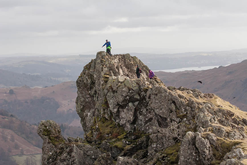 Walkers stand on top of 'the lion' on Helm Crag, Grasmere
