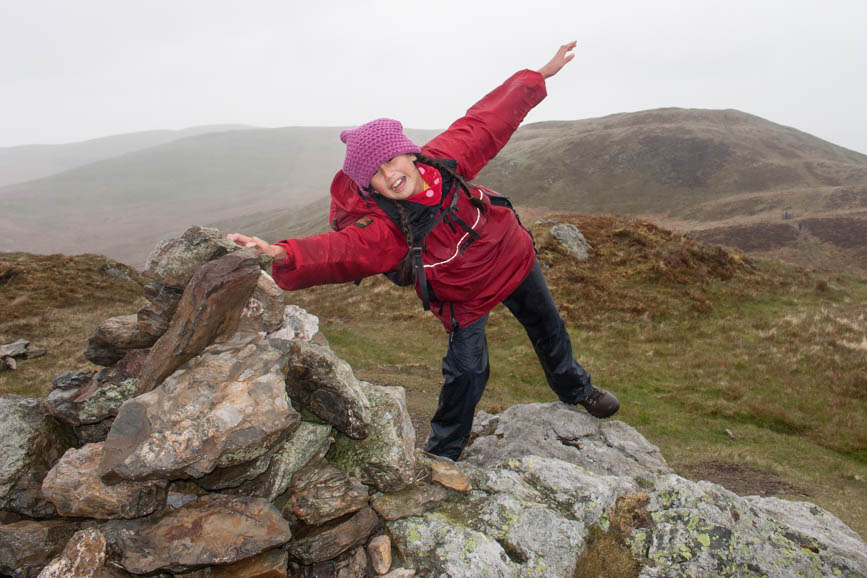 In high winds, Hannah hangs onto the cairn on Low Fell