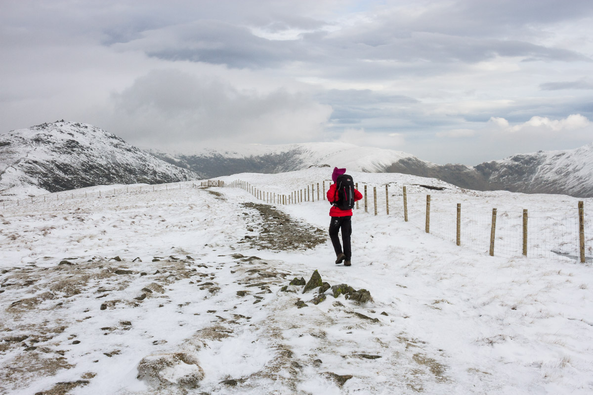 Walker heading towards Ill Bell from Yoke in winter