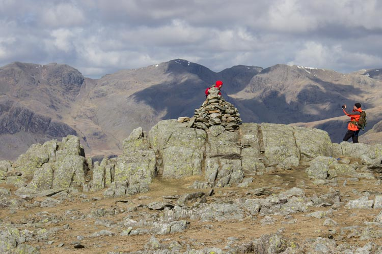 Walkers pose for pictures on summit of Grey Friar with Scafell and Scafell Pike in background